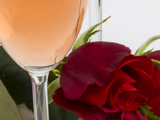 Detail of glass of rosé wine and red roses
